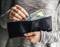 Στις γυναίκες τα χέρια ` s είναι το πορτοφόλι δέρματος με ένα wad εκατό δολαρίων Επιχειρησιακή προσφορά όμορφο μανικιούρ Στοκ Εικόνα