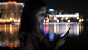 Στις εργασίες γυναικών οδών νύχτας για Smartphone Στο υπόβαθρο είναι φω'τα πόλεων νύχτας απόθεμα βίντεο