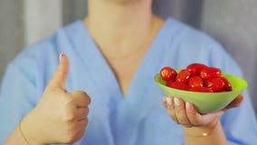 Στις ντομάτες κερασιών χεριών των γυναικών Το χέρι παρουσιάζει κατηγορία φιλμ μικρού μήκους