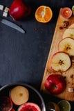 Στις φέτες πινάκων των μήλων, δίπλα σε ένα τηγάνι με ένα ευώδες θερμαμένο κρασί επάνω από την όψη indoors Στοκ εικόνα με δικαίωμα ελεύθερης χρήσης