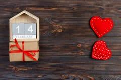 Στις 14 Φεβρουαρίου ξύλινο ημερολόγιο με το κόκκινο κιβώτιο καρδιών και δώρων στη τοπ κάρτα ημέρας βαλεντίνων ` s διάστημα αντιγρ Στοκ εικόνα με δικαίωμα ελεύθερης χρήσης