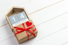 Στις 14 Φεβρουαρίου ξύλινο ημερολόγιο με το κόκκινο κιβώτιο καρδιών και δώρων στη τοπ κάρτα ημέρας βαλεντίνων ` s διάστημα αντιγρ Στοκ φωτογραφία με δικαίωμα ελεύθερης χρήσης