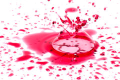 Στιλπνά κόκκινα υγρά σταγονίδια (splatters) που απομονώνονται στο λευκό Στοκ Εικόνα