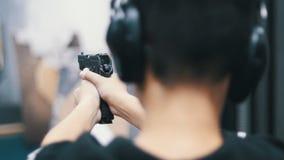 Στοά πυροβολισμού Ένας νεαρός άνδρας που στοχεύει σε έναν στόχο που χρησιμοποιεί ένα πυροβόλο όπλο βλάστηση φιλμ μικρού μήκους
