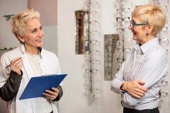 Στοιχεία του ώριμου θηλυκού οφθαλμολόγων ασθενή γραψίματος σε μια περιοχή αποκομμάτων, που λειτουργεί σε ένα οπτικό κατάστημα στοκ εικόνα