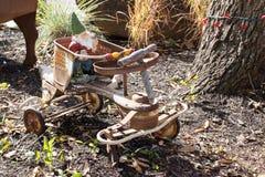 Στοιχειό κήπων που οδηγά ένα τετράτροχο παλαιό σκουριασμένο ποδήλατο παιδιών Στοκ εικόνες με δικαίωμα ελεύθερης χρήσης