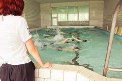 Στοιχειώδη παιδιά σχολείου μέσα στο μάθημα δεξιοτήτων κολύμβησης στοκ εικόνα