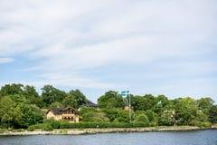 ΣΤΟΚΧΟΛΜΗ, ΣΟΥΗΔΙΑ - 6 ΙΟΥΝΊΟΥ 2016: Παράκτια σπίτια με τις σουηδικές σημαίες και τους ανακυκλώνοντας ανθρώπους, σε ένα νησί του  Στοκ φωτογραφίες με δικαίωμα ελεύθερης χρήσης