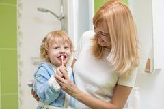 Στοματική φροντίδα παιδιών Το Mom βοηθά το παιδί να βουρτσίσει τα δόντια του στοκ εικόνα με δικαίωμα ελεύθερης χρήσης