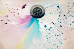 Στον άσπρο κεραμικό νεροχύτη που χύνεται πολλά διαφορετικά χρώματα στα αυγά χρωμάτων για το όμορφο υπόβαθρο Πάσχας και σχεδόν ένα Στοκ Φωτογραφίες