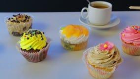 Στον γκρίζο πίνακα είναι τσάι σε ένα άσπρο φλυτζάνι και τα κέικ απόθεμα βίντεο
