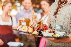 Στον κήπο μπύρας - μπύρα και πρόχειρα φαγητά που εξυπηρετούνται σε Oktoberfest στοκ φωτογραφία με δικαίωμα ελεύθερης χρήσης