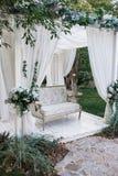 Στον κήπο υπάρχει μια εξέδρα στην οποία ένας όμορφος άσπρος καναπές στο ύφος της Προβηγκίας ή αγροτικός Επάνω από τον καναπέ είνα Στοκ Φωτογραφία