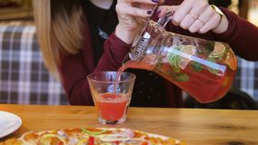 Στον καφέ στον πίνακα τα στενά επάνω χέρια γυναικών χύνουν το χυμό από την καράφα σε ένα ποτήρι απόθεμα βίντεο