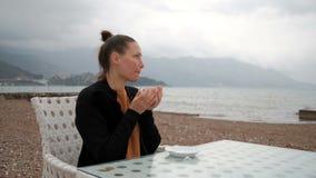 Στον καφέ στις τράπεζες μιας γυναίκας που πίνει το θερμό ποτό απόθεμα βίντεο