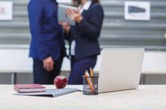 Στον πίνακα γραφείων, ένα μήλο, ένα lap-top, έναν φάκελλο σημειωματάριων και τις μάνδρες Στο υπόβαθρο, εργαζόμενοι γραφείων στοκ εικόνες με δικαίωμα ελεύθερης χρήσης