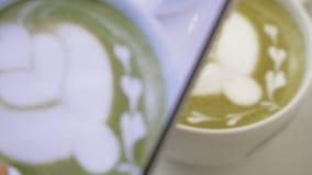 Στον πίνακα είναι ένα φλιτζάνι του καφέ με τον αφρό και το σχέδιο και το κορίτσι παίρνουν τη φωτογραφία του φλυτζανιού στο κινητό φιλμ μικρού μήκους