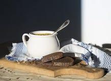Στον πίνακα μια μπλε πετσέτα με το σχέδιο διακοσμήσεων και η σουπιέρα σούπας με την κίτρινη σούπα πασπαλίζουν στον ήλιο τους ξύλι Στοκ Φωτογραφία