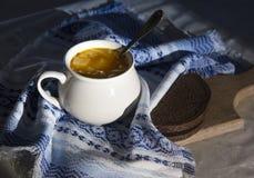 Στον πίνακα μια μπλε πετσέτα με το σχέδιο διακοσμήσεων και σουπιέρα σούπας με την κίτρινη σούπα στο ψωμί ήλιων Στοκ Φωτογραφίες