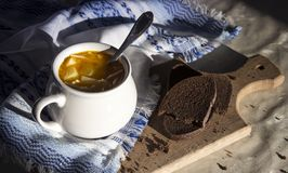 Στον πίνακα μια μπλε πετσέτα με το σχέδιο διακοσμήσεων και σουπιέρα σούπας με την κίτρινη σούπα στο ψωμί ήλιων Στοκ φωτογραφία με δικαίωμα ελεύθερης χρήσης