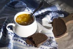 Στον πίνακα μια μπλε πετσέτα με το σχέδιο διακοσμήσεων και σουπιέρα σούπας με την κίτρινη σούπα στο ψωμί ήλιων Στοκ Εικόνες