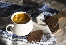 Στον πίνακα μια μπλε πετσέτα με το σχέδιο διακοσμήσεων και σουπιέρα σούπας με την κίτρινη σούπα στο ψωμί ήλιων Στοκ εικόνες με δικαίωμα ελεύθερης χρήσης