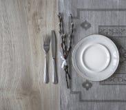 Στον πίνακα μια πετσέτα με ένα πιάτο δικράνων ένα μαχαίρι και μια ιτιά διακλαδίζεται Στοκ Εικόνα