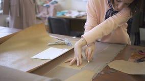 Στον πίνακα ο ράφτης περιέβαλε με μια κιμωλία ένα σχέδιο στο υλικό για το ράψιμο απόθεμα βίντεο