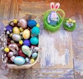 Στον παλαιό ξύλινο shabby πίνακα ένα πιάτο με χρωματισμένος στα διαφορετικά αυγά Πάσχας χρωμάτων με την ιτιά φτερών και τα κοτόπο Στοκ εικόνα με δικαίωμα ελεύθερης χρήσης