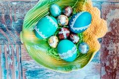 Στον παλαιό ξύλινο shabby πίνακα ένα πιάτο με χρωματισμένος στα διαφορετικά αυγά Πάσχας χρωμάτων με την ιτιά φτερών Στοκ Φωτογραφίες