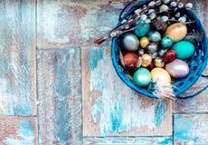 Στον παλαιό ξύλινο shabby πίνακα ένα πιάτο με χρωματισμένος στα διαφορετικά αυγά Πάσχας χρωμάτων με την ιτιά φτερών Στοκ Εικόνα