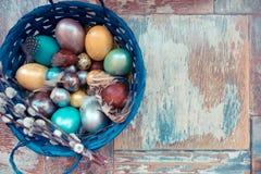 Στον παλαιό ξύλινο shabby πίνακα ένα πιάτο με χρωματισμένος στα διαφορετικά αυγά Πάσχας χρωμάτων με την ιτιά φτερών Στοκ εικόνα με δικαίωμα ελεύθερης χρήσης