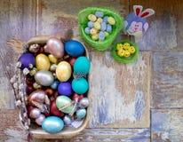 Στον παλαιό ξύλινο shabby πίνακα ένα πιάτο με χρωματισμένος στα διαφορετικά αυγά Πάσχας χρωμάτων με την ιτιά φτερών και τα κοτόπο Στοκ εικόνες με δικαίωμα ελεύθερης χρήσης
