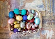 Στον παλαιό ξύλινο shabby πίνακα ένα πιάτο του μετάλλου με χρωματισμένος στα διαφορετικά αυγά Πάσχας χρωμάτων με την ιτιά φτερών Στοκ Εικόνες