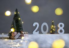 Στον τομέα κάτω από fir-trees, και στην απόσταση είναι τα σχήματα το 2018 όπου στο ρόλο ενός χριστουγεννιάτικου δέντρου με τα φω' Στοκ φωτογραφίες με δικαίωμα ελεύθερης χρήσης