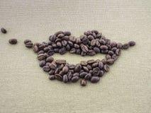 Στον τραχύ καμβά λινού applique από τα ψημένα φασόλια καφέ με μορφή των χειλιών του στόματος ενός προσώπου Χαμόγελο Στοκ Εικόνες