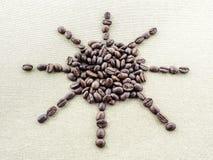 Στον τραχύ καμβά λινού applique από τα ψημένα φασόλια καφέ υπό μορφή ήλιου με τις ακτίνες Στοκ φωτογραφία με δικαίωμα ελεύθερης χρήσης