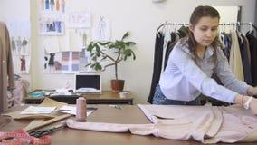 Στον υπολογιστή γραφείου η μοδίστρα τοποθετεί τα ενδύματα για την επισκευή και τη βελτίωση του σακακιού στη διαταγή φιλμ μικρού μήκους