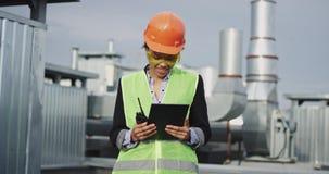Στον όμορφο χαμογελώντας μεγάλο αφρικανικό μηχανικό γυναικών εργοτάξιων οικοδομής με ένα κράνος και τα γυαλιά εξοπλισμού ασφάλεια απόθεμα βίντεο