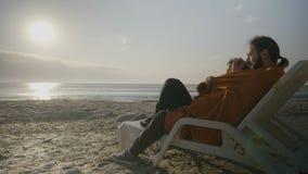 Στοργικό νέο ζεύγος που βρίσκεται σε μια καρέκλα σαλονιών στην παραλία που προσέχει το ηλιοβασίλεμα καλυμμένος με ένα κάλυμμα - φιλμ μικρού μήκους