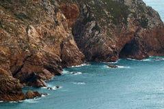 Στους βράχους και τις πέτρες που κτυπούν τον Ατλαντικό Ωκεανό, που διαμορφώνει έναν κόλπο με το σαφές μπλε νερό Στοκ Φωτογραφίες