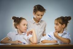 Στοχαστικά κορίτσια και λίγος μαθητής στο γκρίζο υπόβαθρο μαύρο σχολείο έννοιας βιβλίων ανασκόπησης copyspace Στοκ εικόνα με δικαίωμα ελεύθερης χρήσης
