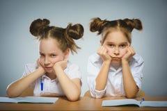 Στοχαστικά κορίτσια που κάθονται στο γραφείο στο γκρίζο υπόβαθρο μαύρο σχολείο έννοιας βιβλίων ανασκόπησης copyspace Στοκ εικόνες με δικαίωμα ελεύθερης χρήσης