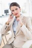 Στοχαστική έξυπνη καφετιά μαλλιαρή επιχειρηματίας που κάνει ένα τηλεφώνημα Στοκ Φωτογραφία
