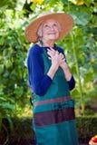 Στοχαστική ανώτερη γυναίκα στο καπέλο και την ποδιά κήπων στοκ φωτογραφίες