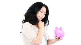 Στοχαστική ασιατική γυναίκα που κρατά και που φαίνεται μια piggy τράπεζα απόθεμα βίντεο