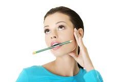Στοχαστική γυναίκα με το μολύβι Στοκ Εικόνες