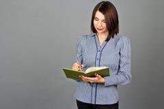 Στοχαστική γυναίκα που κοιτάζει και που γράφει στις σημειώσεις της Στοκ Φωτογραφίες