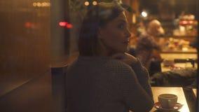 Στοχαστική γυναίκα που κοιτάζει στο παράθυρο, που κάθεται στον καφέ, φω'τα που απεικονίζει στο γυαλί απόθεμα βίντεο