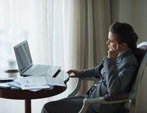 Στοχαστική επιχειρησιακή γυναίκα που εργάζεται στο δωμάτιο ξενοδοχείου στοκ εικόνες